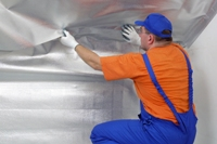 A technician installing foil insulation in an attic