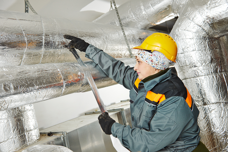 woman installing reflective foil insulation