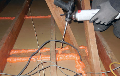 A man working on air sealing attic
